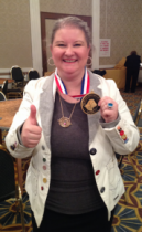 Laurren Darr holds up her Maxwell Medallion